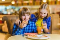 Garçon et fille de sourire mangeant de la pizza ou buvant du jus d'intérieur Images stock