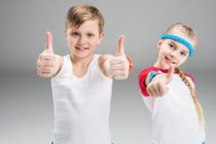 Garçon et fille de sourire mignons dans les vêtements de sport montrant des pouces sur le gris Photos stock