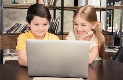 Garçon et fille de sourire s'asseyant à la table et à l'aide de l'ordinateur portable ensemble Image stock