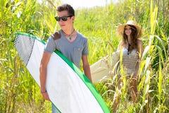 Garçon et fille de surfer marchant dans la jungle verte Photographie stock libre de droits