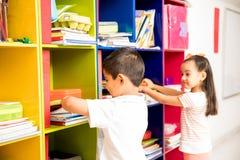 Garçon et fille devant le casier de salle de classe Photos libres de droits