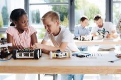 Garçon et fille discutant la construction d'une voiture robotique Image stock