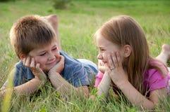 Garçon et fille drôles sur l'herbe Photographie stock libre de droits