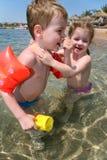 Garçon et fille en mer Images stock