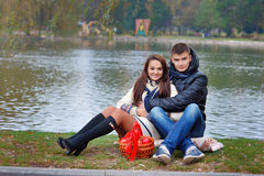 Garçon et fille en parc sur un fond de l'eau avec des pommes Images stock