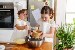Garçon et fille faisant cuire au four ensemble dans la cuisine à la maison Images libres de droits