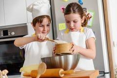 Garçon et fille faisant cuire au four ensemble dans la cuisine à la maison Photos stock
