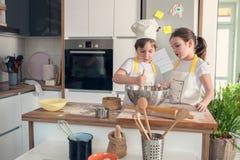 Garçon et fille faisant cuire au four ensemble dans la cuisine à la maison Image libre de droits