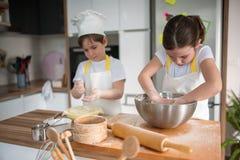 Garçon et fille faisant cuire au four ensemble dans la cuisine à la maison Photographie stock libre de droits