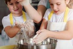Garçon et fille faisant cuire au four ensemble dans la cuisine à la maison Photographie stock