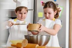 Garçon et fille faisant cuire au four ensemble dans la cuisine à la maison Photo libre de droits