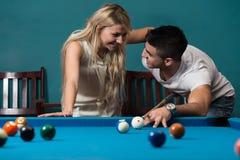 Garçon et fille flirtant sur un jeu de piscine Images libres de droits