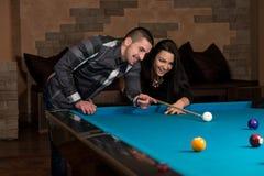 Garçon et fille flirtant sur un jeu de piscine Image stock