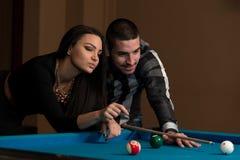 Garçon et fille flirtant sur un jeu de piscine Photographie stock libre de droits