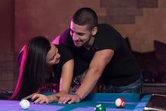 Garçon et fille flirtant sur un jeu de piscine Images stock