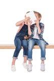 Garçon et fille gais à l'aide du comprimé numérique tout en se reposant sur le banc, Images stock