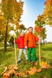 Garçon et fille gais avec des râteaux se tenant en parc Images libres de droits