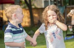 Garçon et fille heureux d'enfant en bas âge riant, tenant des mains et jouant dans une arrière-cour Photo stock