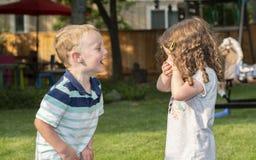 Garçon et fille heureux d'enfant en bas âge riant, tenant des mains et jouer Images libres de droits