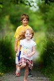 Garçon et fille jouant à l'extérieur en été Images libres de droits