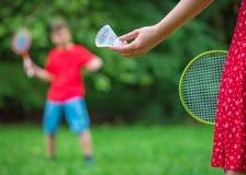 Garçon et fille jouant au badminton Photo stock
