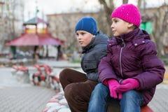 Garçon et fille jouant au terrain de jeu Image libre de droits