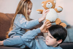 Garçon et fille jouant avec l'ours de nounours et s'asseyant sur le sofa Image libre de droits