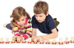 Garçon et fille jouant avec le chemin de fer en bois Image stock