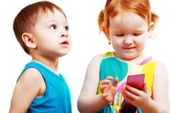 Garçon et fille jouant avec le mobile Image stock