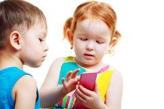 Garçon et fille jouant avec le mobile Photographie stock libre de droits