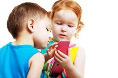 Garçon et fille jouant avec le mobile Photo stock
