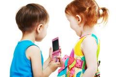Garçon et fille jouant avec le mobile Images stock