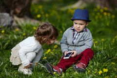 Garçon et fille jouant avec le téléphone portable Photo libre de droits
