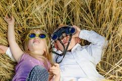 Garçon et fille jouant dans l'herbe avec des jumelles Photographie stock libre de droits