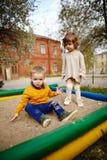 Garçon et fille jouant dans le bac à sable Photographie stock libre de droits