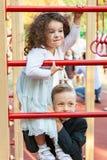 Garçon et fille jouant dans le terrain de jeu Photo stock