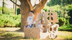 Garçon et fille jouant dans un bateau de carton Photo stock
