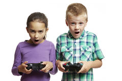 Garçon et fille jouant la console de jeux Images stock