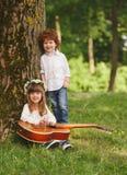 Garçon et fille jouant la guitare en parc d'été Image stock