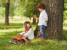 Garçon et fille jouant la guitare en parc d'été Images stock