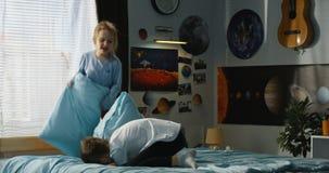 Garçon et fille jouant le combat d'oreiller sur le lit banque de vidéos