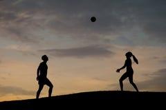 Garçon et fille jouant le volleyball sur la nature Image stock