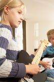Garçon et fille jouant les guitares électriques à la maison Photos libres de droits