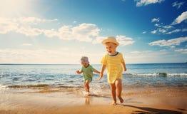 Garçon et fille jouant sur la plage Photographie stock libre de droits