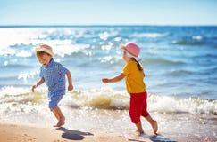 Garçon et fille jouant sur la plage Image libre de droits