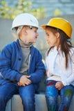 Garçon et fille jouant sur le chantier de construction Images libres de droits