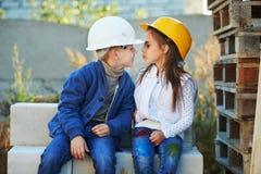 Garçon et fille jouant sur le chantier de construction Photos stock
