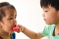 Garçon et fille mangeant leur crème glacée préférée Image libre de droits