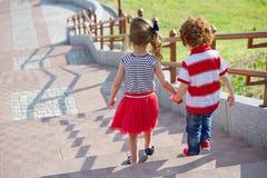 Garçon et fille marchant sur l'escalier Photographie stock libre de droits