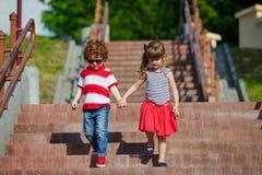 Garçon et fille marchant sur l'escalier Images libres de droits